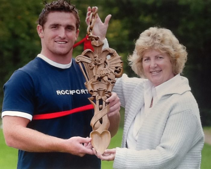 Huw Bennett receiving the Team's new mascot from The Lovespoon Gallery of Mumbles in 2003.  He was the youngest member of the team at the time and this has continued to be the Team tradition ever since.